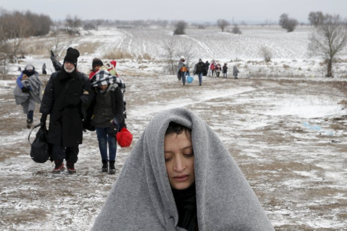 "Migrants walk through a frozen field after crossing the border from Macedonia, near the village of Miratovac, Serbia, January 18, 2016. Reuters photographer Marko Djurica: ""Since the beginning of the migrant crisis, my colleagues and I asked ourselves the same question: what will happen when the winter comes? We were thinking of a Balkans winter: minus 20 degrees Celsius and wind so strong that you have to walk backwards into it. Most migrants come from Syria and Iraq and they have only seen snow in the movies. I remember a young girl saying, while holding a snowball, that she didn't know snow was cold. After weeks and weeks of weather more like springtime than winter, a forecast on my phone got me packing my gear. I headed to the Serbia-Macedonia border, as down there migrants have to walk 10km in rough terrain before they can board a train to Serbia. Snow was falling and I saw a first group crossing the border. The wind was so noisy that they weren't able to talk to each other. Another group arrived with lots of kids. Many of them were crying from the cold. I was speechless. A man approached me. 'Mister how much further do we have to walk?' About 5km, I said. He turned and pointed to a group some 50 metres behind. 'One, two, three, four, five. That's my family. The one on the left who is walking in pain is my sister. She broke her leg in Aleppo last year, I am afraid for her.' I tried to calm him down, explaining that there were people here to help. I explained that they had to catch a train in Presovo and travel to Croatia, then on to Slovenia, and Austria before reaching Germany. 'Six of us have 60 euros left. Do you think it will be enough for us to finish our journey?' I was speechless again."" REUTERS/Marko Djurica ATTENTION EDITORS A PICTURE AND ITS STORY ""MIGRANTS STRUGGLE THROUGH BALKANS WINTER"" FOR MORE IMAGES SEARCH ""DJURICA MIGRANTS"". TEMPLATE OUT. TPX IMAGES OF THE DAY"